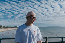 a man in a beanie standing on a pier
