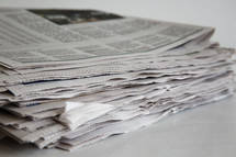 stacked newspapers on a white table.