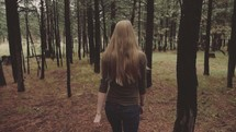 Back of a woman walking through the trees in the woods.