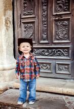 smiling toddler boy in a cowboy hat