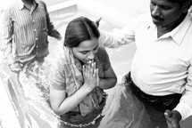 woman in prayer about to be dunked during a baptism