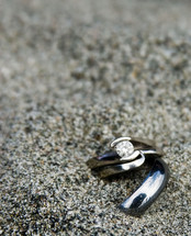 Wedding rings in the sand.