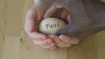 cupped hands holding an egg with the word faith