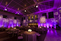 Restaurant and stage lit with purple lights and snowflake design Christmas holiday event party