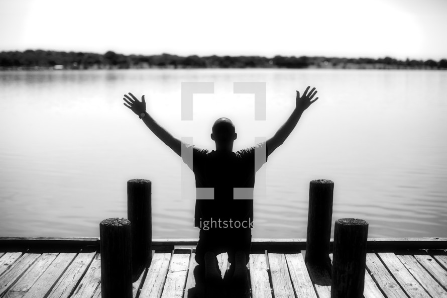 Man kneeling with raised hands on river dock