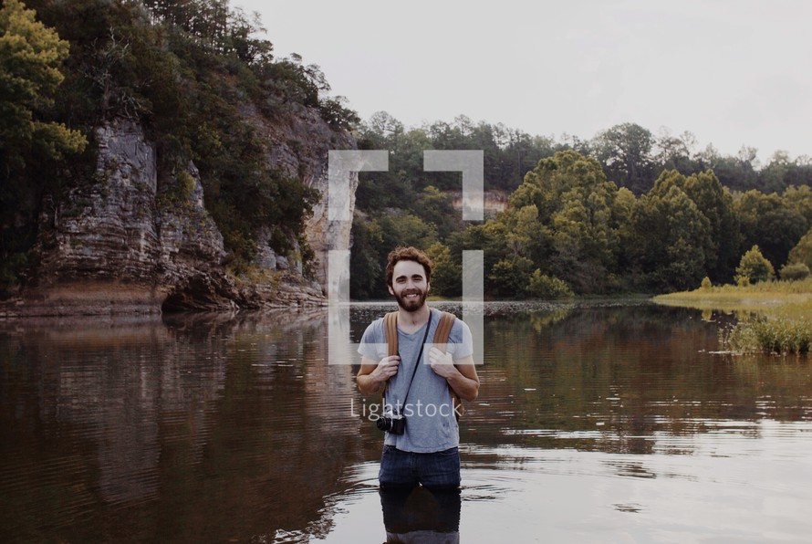 man with a camera standing in a lake