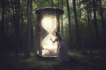 woman touching a giant glowing hourglass