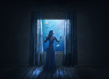 woman looking out a window into an aquarium