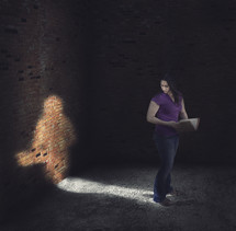 Woman standing in the light of her own shadow holding a Bible.