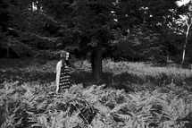 a woman standing in a forest of ferns