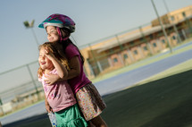 A little girl with her arm around a younger girl.