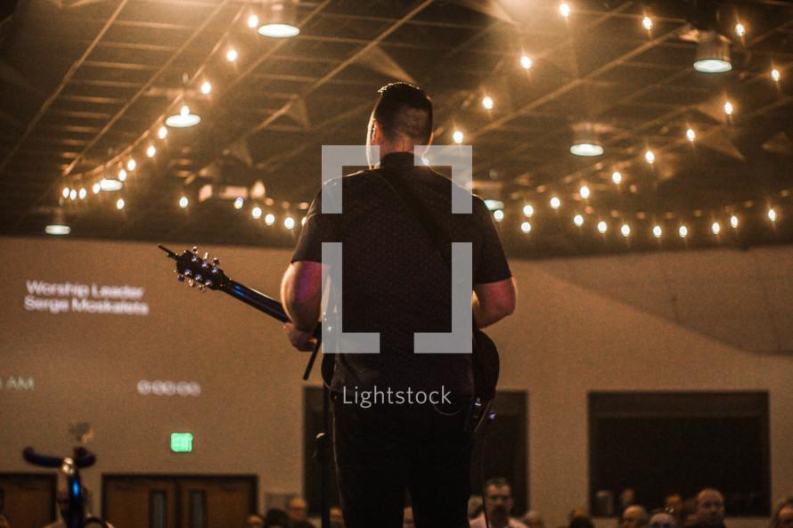 a man playing a guitar at a worship service