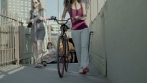 a woman with a bicycle walking out of a subway tunnel