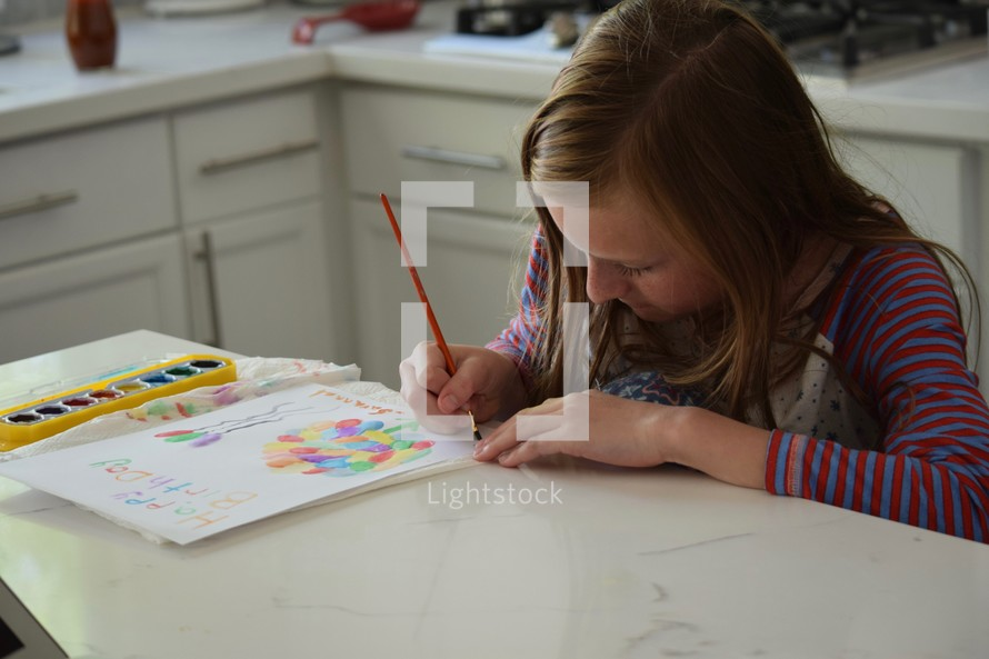 a girl painting a happy birthday card