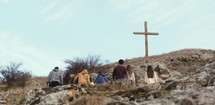 group of people walking up the side of a mountain towards a cross