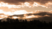 clouds moving over mountaintops