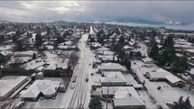 a drone flying over a community after a winter snow