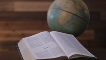 Vintage globe spinning with open Bible next to it. This footage is perfect for a missions focused video, a missions conference etc.