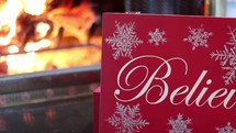 Christmas card in front of a fire in a fireplace