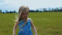 child walking through a grassy field