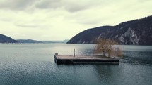 person standing alone on a floating dock