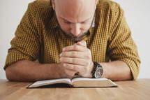 man with his head bowed reading a BIble