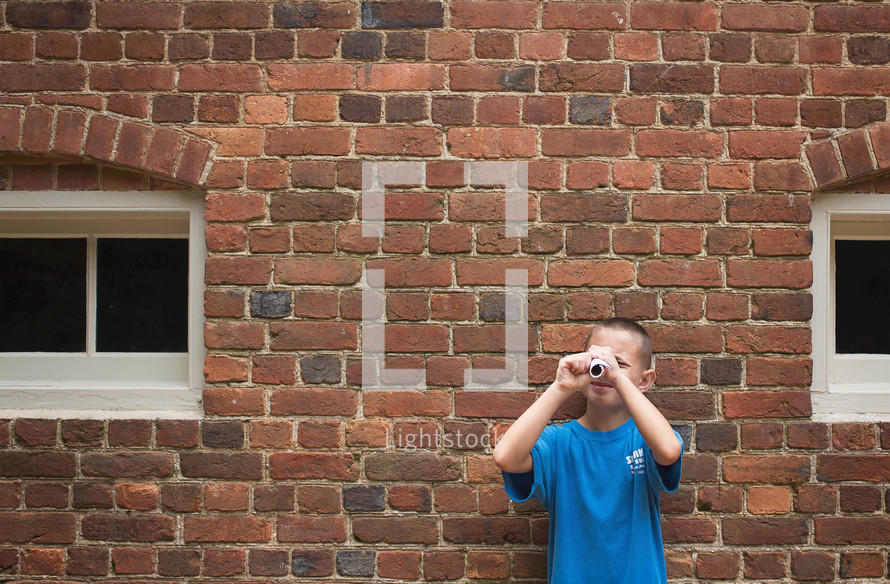 a boy looking through a rolled up piece of paper
