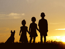silhouettes of kids and their dog at sunset