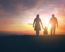 silhouette of a mother and father holding their daughters hand at sunset