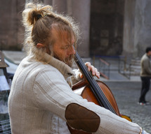 A man playing a cello in the streets of Rome