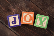 "The word ""joy"" spelled out with children's wooden blocks."
