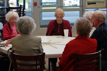 Seniors at a round table playing dominoes.