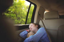 a sleeping child in the backseat of a car