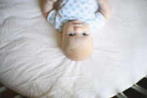 an infant in a round crib looking up