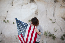 a woman walking carrying an American flag