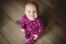 a smiling infant in heart pattern pajamas