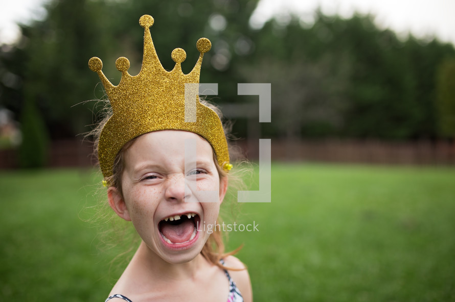 a girl with a crown and missing teeth
