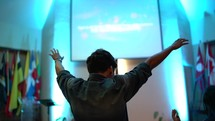 young man with hands raised high during a worship service