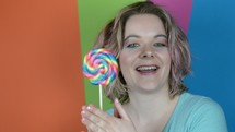 a young woman twirling a lollipop