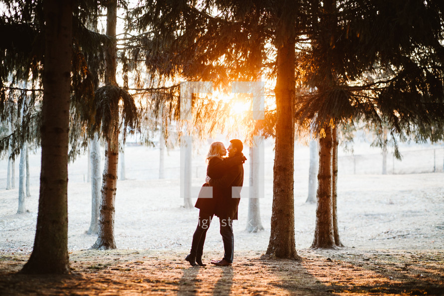 couple standing in the woods at sunset