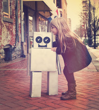 a girl playing with a cardboard robot