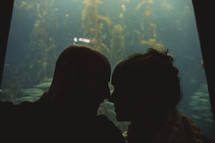 couple kissing in front of a large aquarium