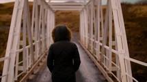 a woman in a coat walking across a covered bridge