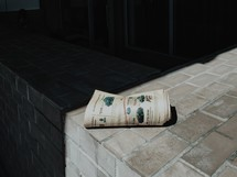 A rolled up newspaper laying in the sun.