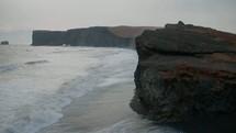 tide washing onto a beach and sea cliffs