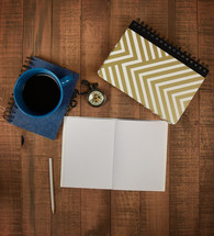 coffee mug, blue, pencil, open journal, blank pages, compass, spiral notebook, wood background, brown