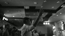 parishioners with raised hands during a worship service