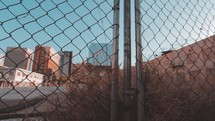 downtown city view through a chain link fence