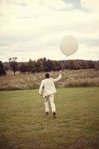 man in a suit running holding a white balloon