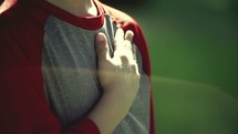 Boy placing his hand over his heart outside.